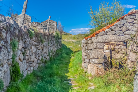 View of pedestrian path up through agricultural fields, with buildings and walls in granitic stone, built in a traditional way, in the Caramulo mountains, Portugal