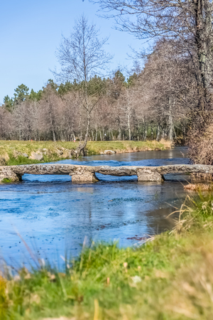 View of a river, with old and archaic stone bridge for pedestrian passage, trees, rocks and vegetation on the banks, reflections in the water and bright colors, Portugal Banco de Imagens