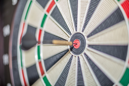 Accurate dart sight hitting center of target, dartboard and dart, blurred background,,,