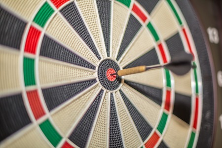Accurate dart sight hitting center of target, dartboard and dart, blurred background...