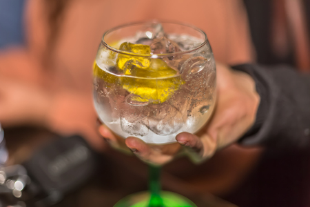 View of hand picking up a glass of refreshing gin, with lemon and lots of ice, classic glass, with green foot, background blurred with person
