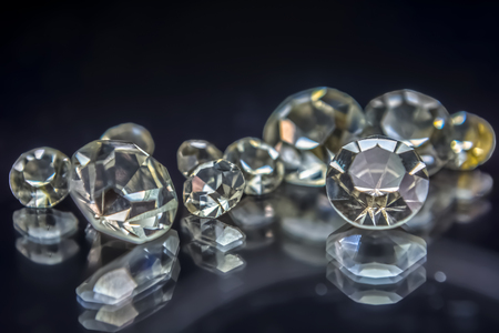 View of gemstones, several diamonds with different sizes, dark background blur