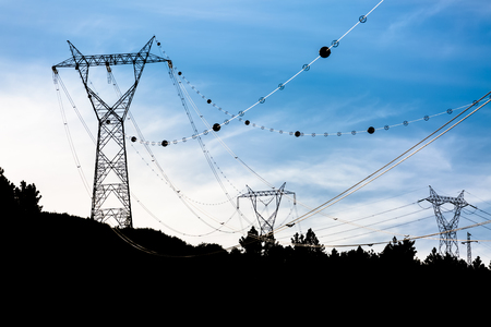 Silhouette view of passing towers of high voltage electrical cables, with anti oscillation balls, sunset, in Portugal Banco de Imagens