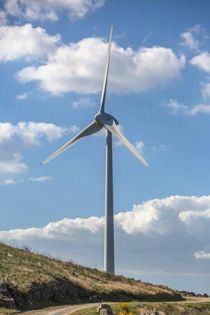 Widok turbiny wiatrowej na szczycie gór, błękitne niebo jako tło w Portugalii