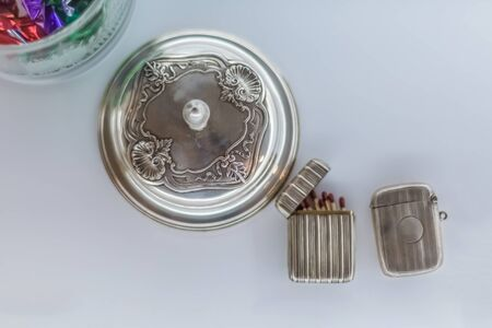 View of a decorative antique metallic objects, vintage - retro metal cup and metal matchbox, isolated, white background with shadow