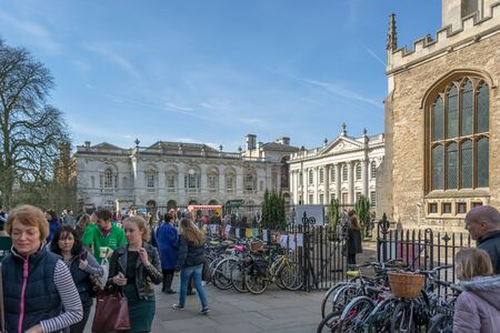 Cambridge, England / United Kingdom - 03 15 2014: View at the Plaza Kings Parade street on Cambridge downtown, Great St Marys Church and Senate house passage building, bikes parking on street and active people