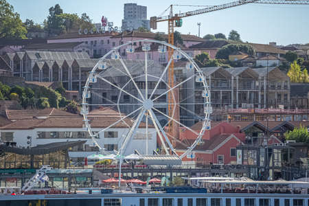 Gaia /Portugal - 10/02/2018 : View of Gaia city on Douro river banks, with a recreational ferris wheel, and the Porto wine cellars on background Redactioneel