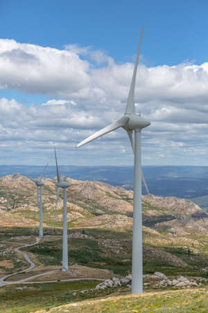 View of a wind turbines on top of mountains, cloudy sky as background in Portugal... 免版税图像
