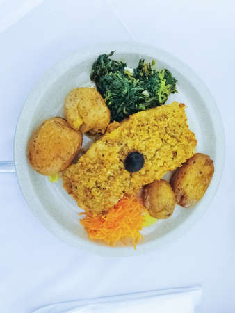 Isolated view of typical Portuguese dish, cod with bread, roasted potatoes, spinach with garlic and grated carrots, olives on top. White as background...