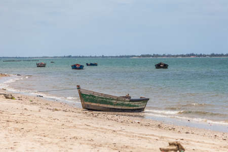 View of traditional fishing boats floating on the edge of the Luanda bay beach, Mussulo island as background...