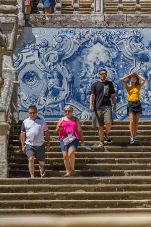Lamego / Portugal - 07 25 2019 : View of young tourist couple and senior tourist couple walking down stairs of Lamego Cathedral