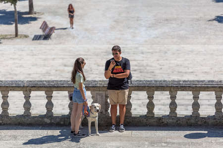 Lamego / Portugal - 07 25 2019 : View of young couple taking in the stairs of Lamego Cathedral with labrador guide dog