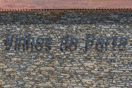 Rustic exterior Porto Wine cellars wall in paired masonry schist and granite mix with letters