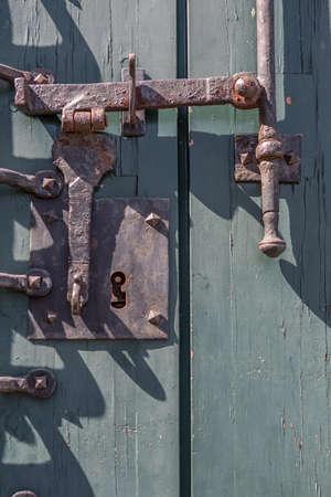 Detailed view of a vintage door lock on old wooden door, rusty metallic mechanism... 免版税图像