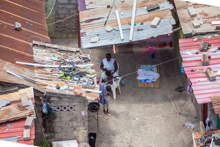 Luanda / Angola - 12/07/2020: Aerial view of a african mother and her children in exterior patio on poor neighborhood in the central area of Luanda city, typical African ghetto, with poor tents, called musseques in Angola 新闻类图片