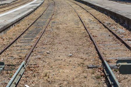 Detailed view of train line, rails in perspective, train station as background, in Regua city, Portugal