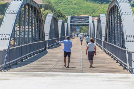 Regua / Portugal - 10/02/2020 : View of a senior couple of tourists on backs, strolling through the metallic bridge of the city of Peso Regua 免版税图像