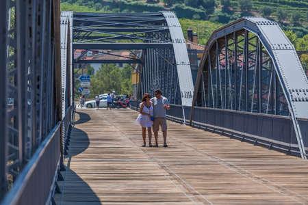 Peso da Regua / Portugal - 07 25 2019 : View of a couple of tourists, strolling through the metallic bridge of the city of Peso Regua