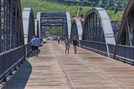 Regua / Portugal - 10/02/2020 : View of a tourist people on backs, strolling through the metallic bridge of the city of Peso da Regua