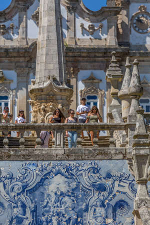 Lamego / Portugal - 07 25 2019 : View of tourists walking down stairs of Lamego Cathedral, ceramic tile panel and pinnacles, Cathedral as background