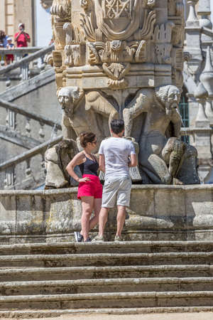 Lamego / Portugal - 07 25 2019 : View of young tourist couple talking on fountain, stairway on Lamego Cathedral