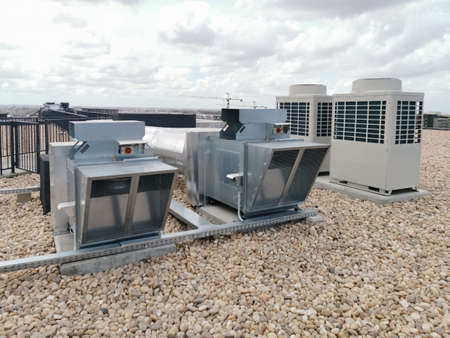 View of air ventilation ducts, extraction and insufflation, HVAC system, and exterior AC units on the building roof...