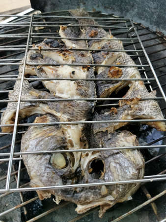 Detailed view of fish grilled over a burning coal fire, healthy and typically Mediterranean food...