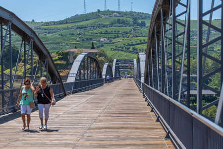 Regua / Portugal - 10/02/2020 : View at the metallic bridgeover Douro river on the Peso da Regua downtow, with tourist people strolling