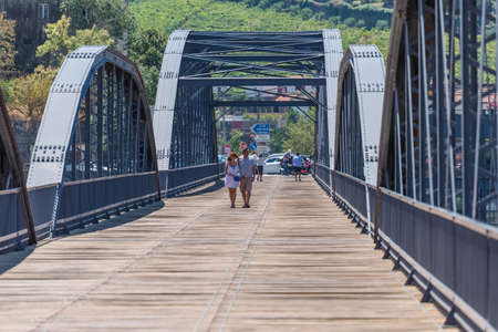 Regua / Portugal - 10/02/2020 : View of an embraced couple of tourists on backs, strolling through the metallic bridge of the city of Régua