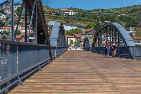 Regua / Portugal - 10/02/2020 : View at the metallic bridge over Douro river on the Peso da Regua downtown, with tourist people strolling