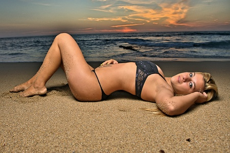HDR image of young beautiful female model layed down on the sand on the beach at sunset in lingerie. Stock Photo - 10752063