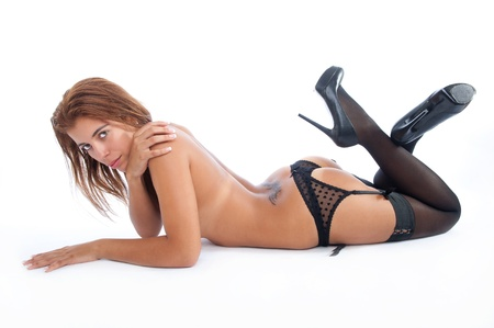 Sexy woman layed on the floor belly down in sensual posing, looking at the camera. Model wearing a thong, garter belt and black socks and high heels. Stock Photo - 10751855