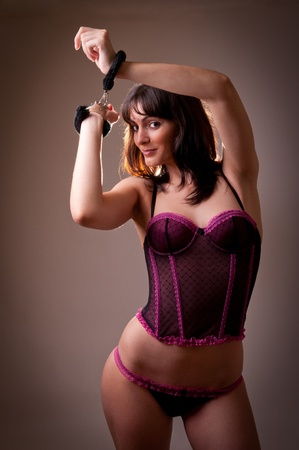 Sexy female model in purple underware and handcuffs. Wearing a Corset and panties and sexy handcuffs. Studio Portrait. Stock Photo - 10752022
