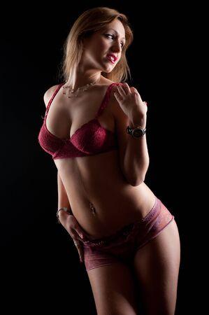 hot breast: Красивые светловолосая женщина ставит и глядя в сторону, носить розовые сексуальное женское белье. Студийный портрет на черном фоне. Фото со стока