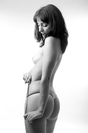 Sensual woman tying a thong underware. Studio black and white high key high contrast sexy portrait Stock Photo - 10751860