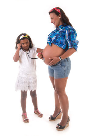 young girl listening to her pregnant mother belly photo