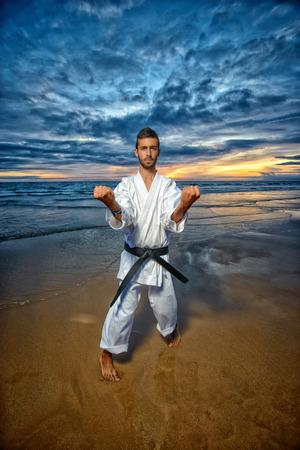 sensei: black belt karate mastar doing kata at sunset at the beack Stock Photo