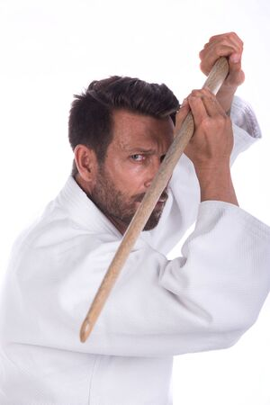 dojo: aikido master with wood sword in defensive position close up portrait Stock Photo