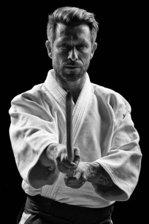 in low spirits: low key portrait of aikido master with wooden sword Stock Photo