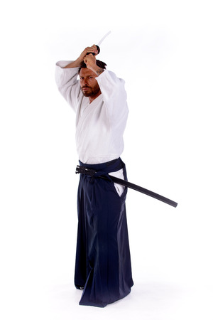 martial ways: aikido master with sword above his head in attack position