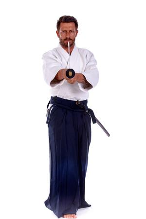 martial ways: aikido master pointing thw sword forward studio portrait