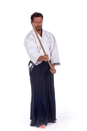 dojo: aikido master with sword in attack position isolated Stock Photo