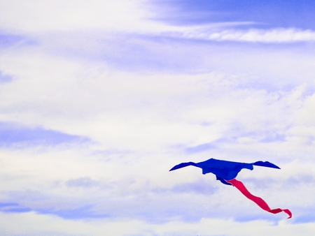 Kite blue with a red tail isolated on blurred sky and cloud. Floating on air. The lighting in the daytime. Toy in the recreation. Outdoor activities in the holiday. Using wind force of nature.