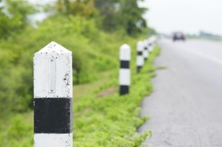 Zwart-witte betonnen pilaren naast straat. Mijlpaal. Guard.