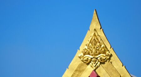 Close up view shot of temple gable gold art against clear blue sky.
