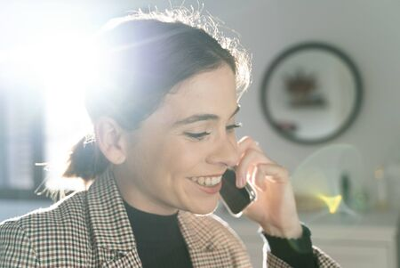 Close-up of an attractive young girl talking on the business phone while telecommuting from her home room. Stock Photo