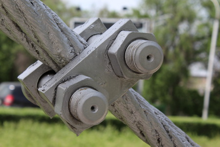 bolts and nuts: Large bolts, nuts and steel wire rope. Elements of fastening of bridge. Stock Photo
