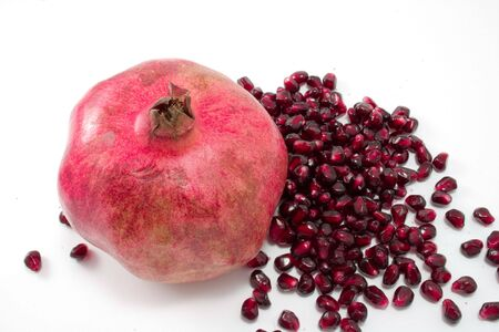pommegranate: One pomegranate with heap of the pomegranate grains on the white background