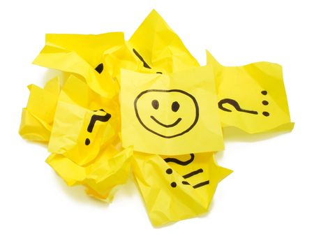 Several crushed yellow stickers with painted marks, one with painted smile