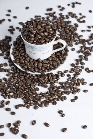 stimulant: Cup of coffee beans on white background